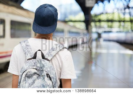 Back View Of Teenage School Boy Wearing White T-shirt And Cap With A Backpack On His Back Walking Ho