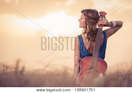 Young retro hippy styled woman posing and holding acoustic guitar on her back in wheat field at the sunset. Music, fashion, art and lifestyle concepts.