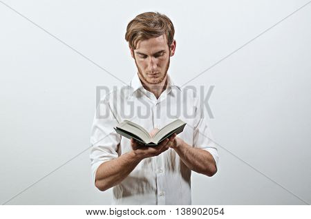 Standing Young Adult Man in White Shirt Keeps a Book in His Hands, Reading