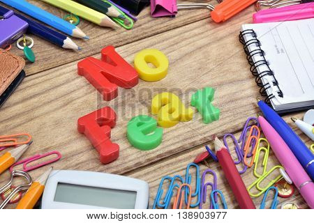 No fear word and office tools on wooden table