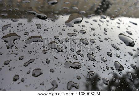 Raindrops on black car after heavy rain.