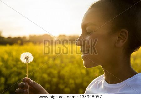 Outdoor portrait of beautiful happy mixed race African American girl teenager female young woman smiling in golden sunset light blowing dandelion clock flower