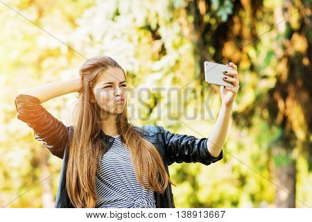 Cool teenage girl taking a selfie on smart phone in park. Closeup of beautiful young woman with long blonde hair making kissy face, posing a selfie outdoors. Natural lighting, vibrant colors.