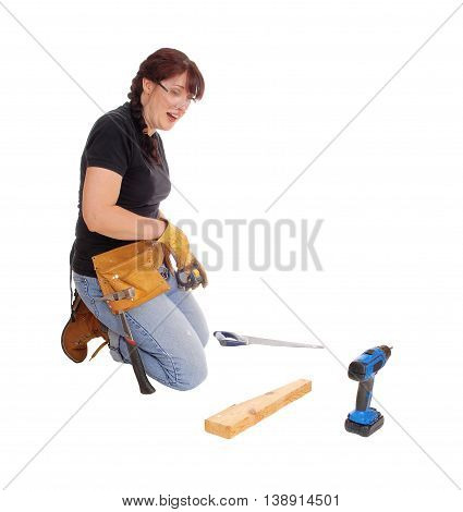 A middle age woman kneeling on the floor and working with some tools isolated for white background.