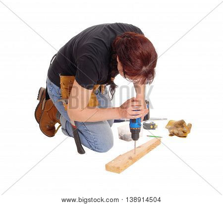 A middle age woman kneeling on the floor and working with some tools drilling in wood isolated for white background.