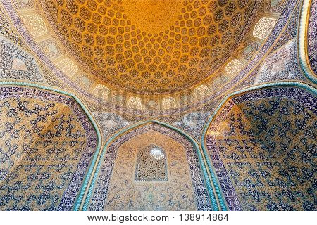 ISFAHAN, IRAN - OCT 14, 2014: Interior of the ancient persian mosque with traditional tiled ceiling and arches on October 14, 2014. The 3rd largest city of Iran Isfahan is example of Iranian Islamic culture