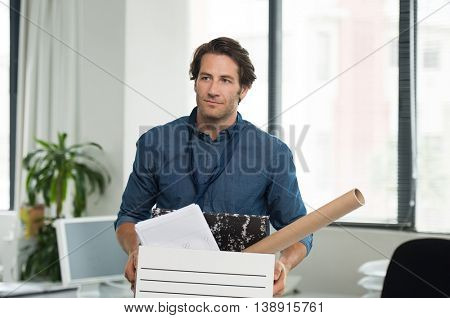 Portrait of fired businessman holding box with documents in office. Portrait of a young businessman carrying box at his workplace. Layoff concept.