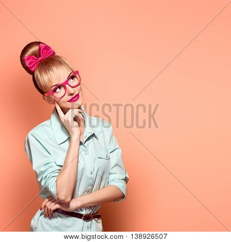 Fashion. Nerd woman in Stylish Glasses Having Fun. Hipster fashion girl think, idea. Playful Blonde nerd with Glamour Pinup stylish Hairstyle, Trendy fashion Outfit, Red bow Makeup. Unusual Creative