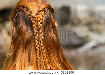 beautiful braid hairstyle on redhead woman closeup