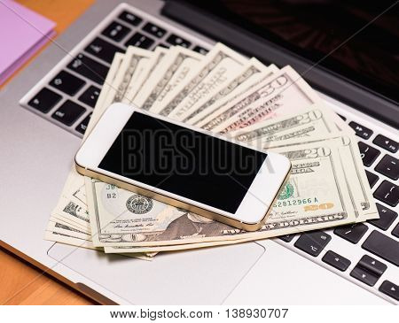Workplace with money and electronic devices - cellphone and laptop computer. Mobile phone and US dollar banknotes on keyboard of notebook. Concept of payment and savings.