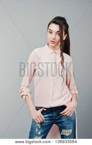 Portrait Of Young Brunette Girl Wearing In Pink Blouse, Ripped Jeans. Fashion Studio Shot
