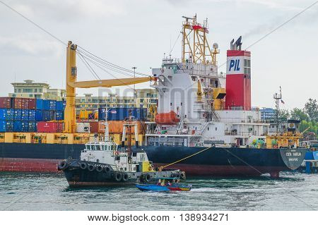 Labuan,Malaysia-July 15,2016:Tug boat towing container ship in Labuan island port.Its a sheltered deep-water harbour which is an important transshipment point for Brunei Darussalam,Sarawak & Sabah