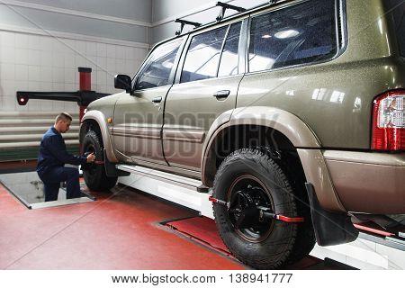 Wheel alignment for SUV in professional workshop. Modern auto service with high-level maintenance