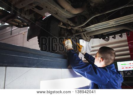 Mechanic recovering car suspension system at auto service. Garage worker restore the car in workshop