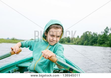 boy rowing a boat in the middle of the river. child enjoys boating and canoeing
