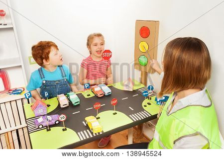 Female teacher in high visibility vest, pointing to the wait signal of the cardboard traffic light, while her pupils showing Stop sign icon