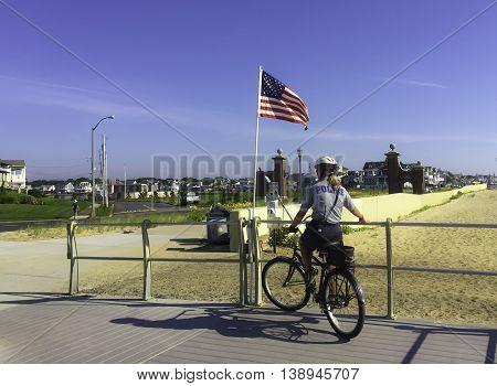 Spring Lake NJ USA July 18 2016 Policewoman on bicycle patrolling the boardwalk near an American flag.