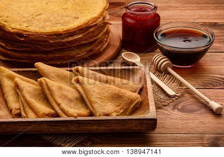 Stack of gluten free pancakes made from corn flour served with raspberry jam and maple syrup.