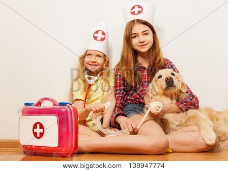 Two beautiful girls, age-diverse sisters in doctor's caps playing veterinarians with their pet, bandaging it's pad, sitting in front of white background with copy-space