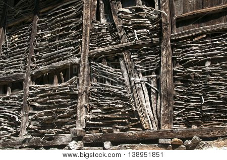Wall of old weathered farm barn of interlaced wooden slats