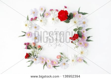 """inspirational quote """"be happy be bright be you"""" written in calligraphy style on paper with pink red roses chamomiles and leaves isolated on white background. Flat lay top view"""