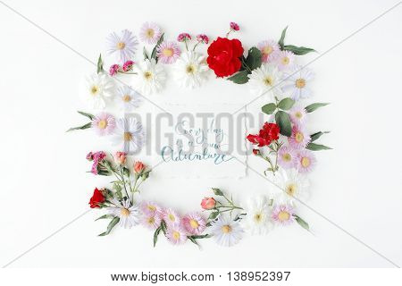 """inspirational quote """"everyday is a new adventure"""" written in calligraphy style on paper with pink red roses chamomiles and leaves isolated on white background. Flat lay top view"""
