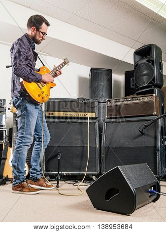 Photo of a man in his late 20's standing in a recording studio playing his electric guitar.