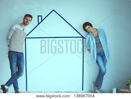 Couple standing in front of painted home on wall.