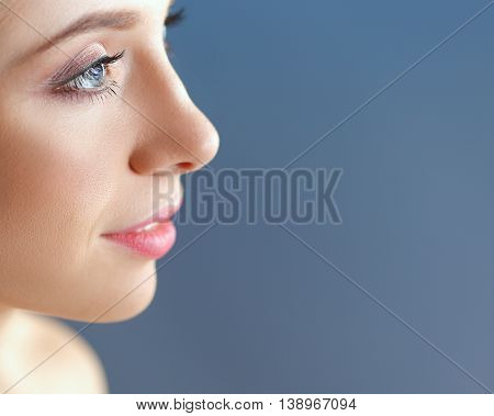 A beautiful woman, portrait isolated on blue background.