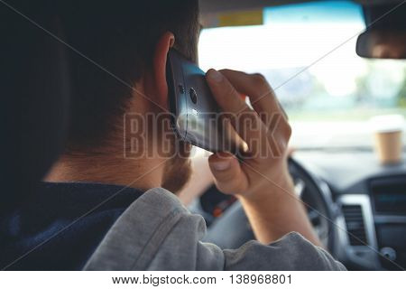 Young man driving a car, talking on mobile phone. Multitasking. Don't talk and drive