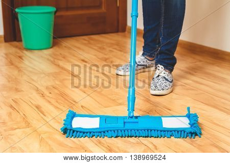 Young woman washing wooden floor. Housekeeping concept.