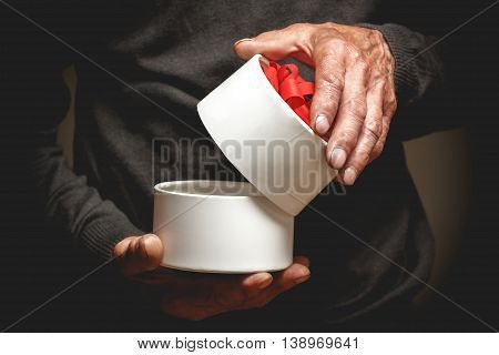 Senior holding a beautiful gift with a red ribbon. In low key