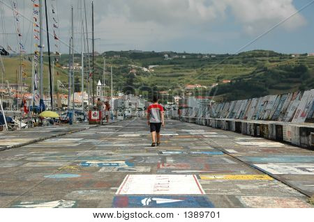 Boy Walking On A Marina