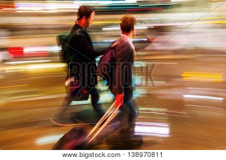traveler with trolley bags walking in the city in abstract motion blur