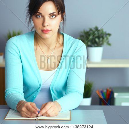 A portrait of a businesswoman sitting at a desk .