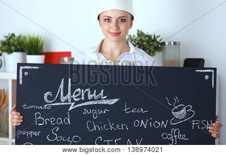 Chef woman holding the menu board , standing in kitchen.