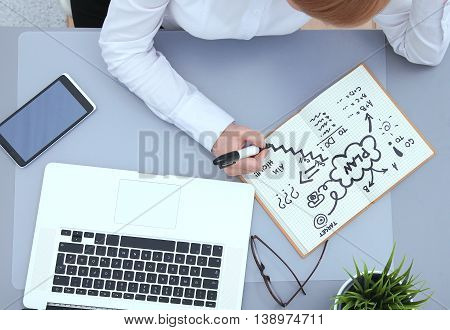 A portrait of a businesswoman sitting at a desk with a laptop