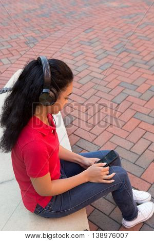 A young african american college student on campus looking at her phone with headphones on