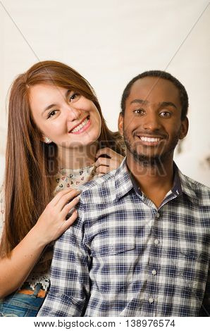 Interracial charming couple wearing casual clothes posing interacting friendly, white studio background.