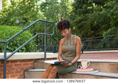 Young african american college student sitting with her books