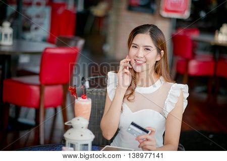Online payment Girl 's hands holding a credit card and using smart phone for online shopping