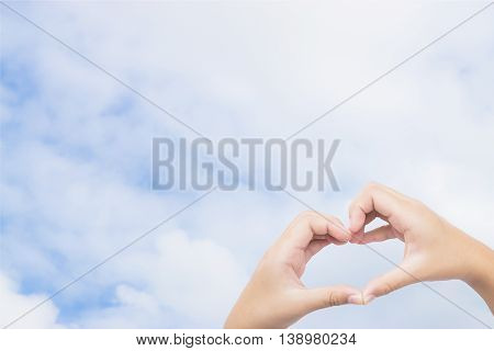 kid hands making a heart shape with blue sky background