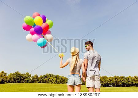 Back View Of Man And Woman With Balloons Holding Hands