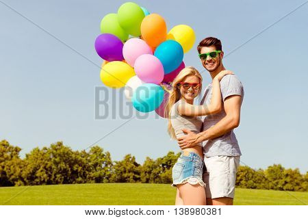 Portrait Of Happy Romantic Lovely Couple Dating  In The Park With Balloons