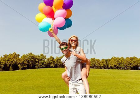 Portrait Of Happy Man Piggybacking His Girlfriend And Having Fun