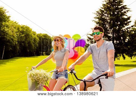 Happy Couple In Love With Balloons Cycling Outdoors In Summer