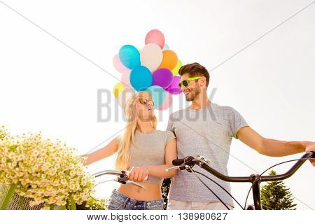 Portrait Of Happy Man And Woman In Love Having Fun With Bicycles