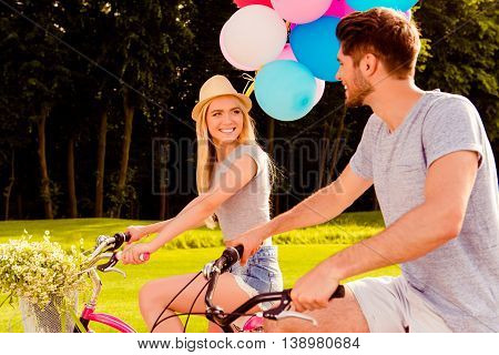Portrait Of Cheerful Woman Riding Bicycle And Looking At Her Boyfriend