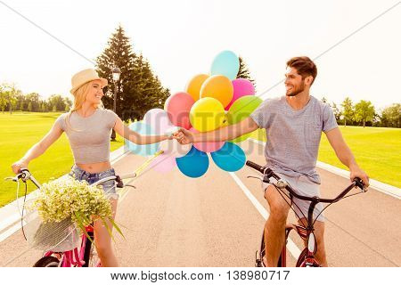 Portrait Of Cheerful Young Family Having Fun And Cycling With Balloons