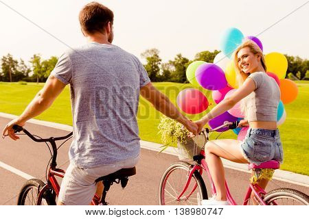 Back View Of Man And Woman At Honeymoon Riding Bikes With Balloons And Holding Hands